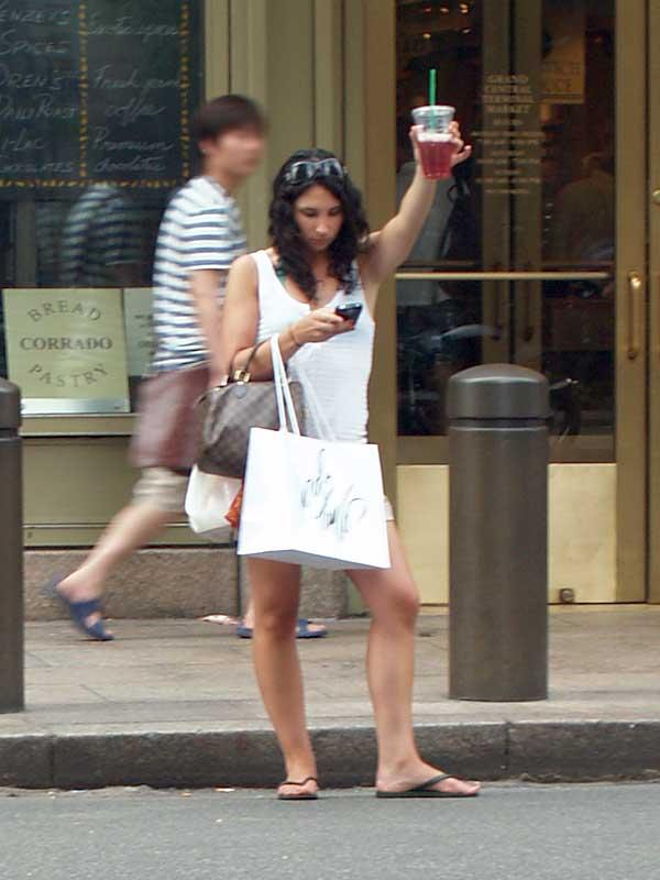 Cena comum: mulher usando celular e esperando um táxi